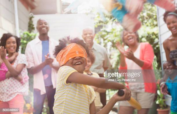 Girl swinging at pinata at birthday party