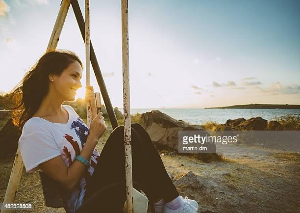 Girl swinging at sunset