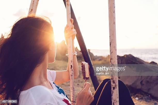Chica balanceo en puesta de sol