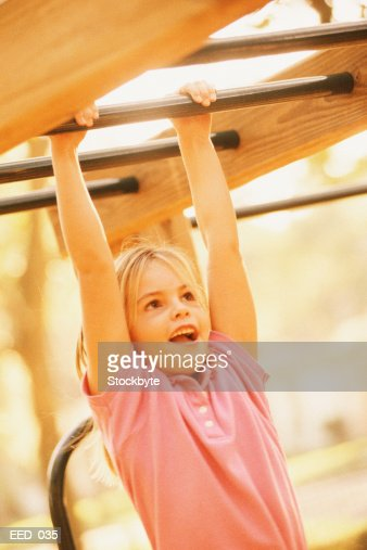 Girl swinging from horizontal bars on jungle gym : Stock Photo