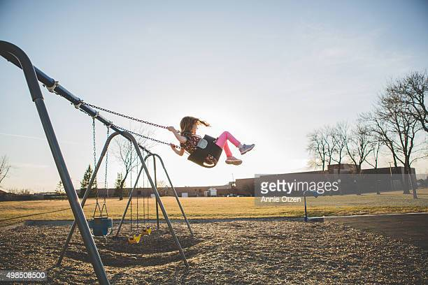 Girl swinging high into the sky