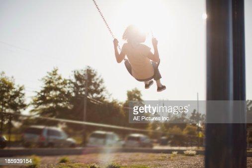 Girl swinging in sunset