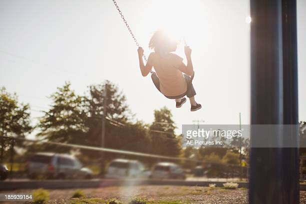 Girl swinging in sunset