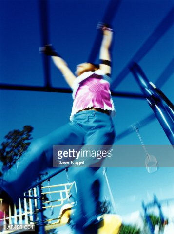 Girl (5-7) swinging on climbing frame, low angle view (blurred) : Stock Photo