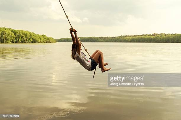 Girl Swinging On Rope Over Lake Against Sky