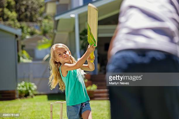 girl swings at bat in game of cricket