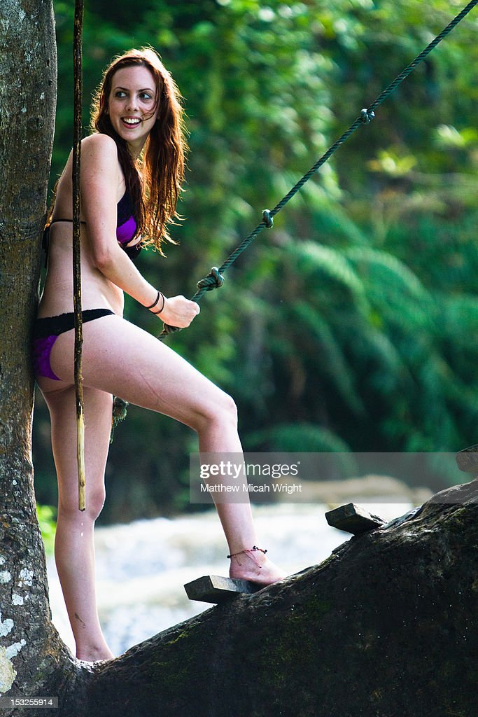 A girl swings from a rope swing. : Stock Photo