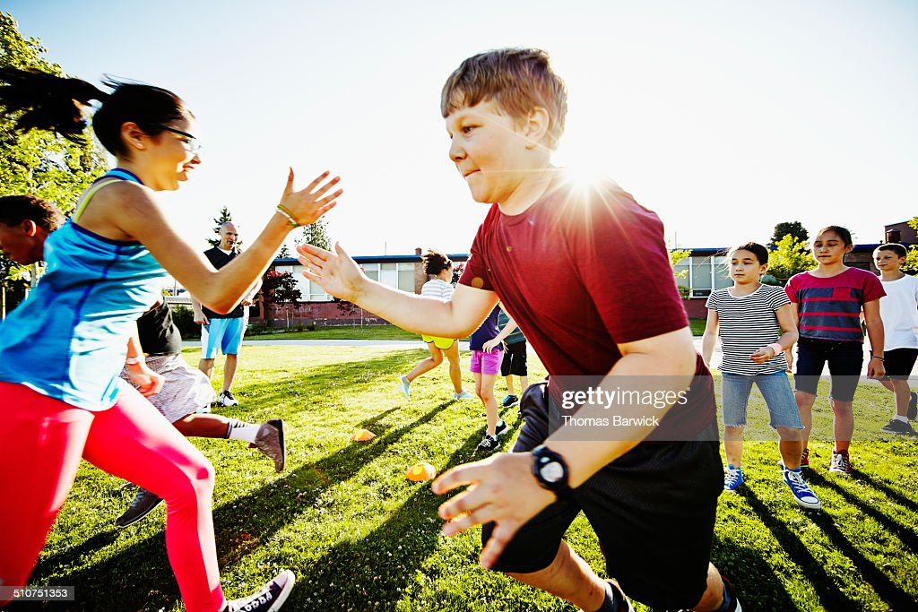 Girl tagging boy in relay race on grass field : Stock Photo