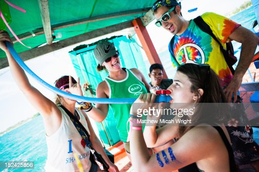 A girl takes a beer from a funnel on this boat. : Stock Photo