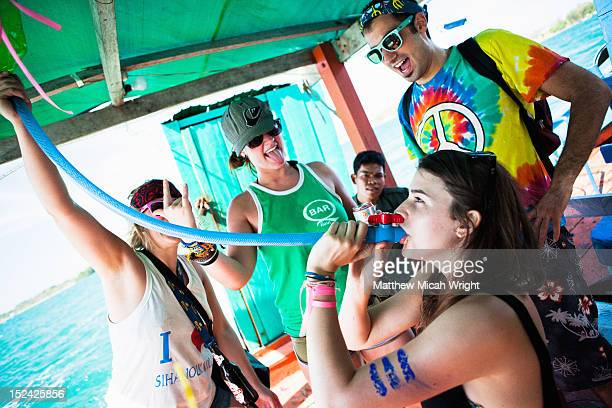 A girl takes a beer from a funnel on this boat.