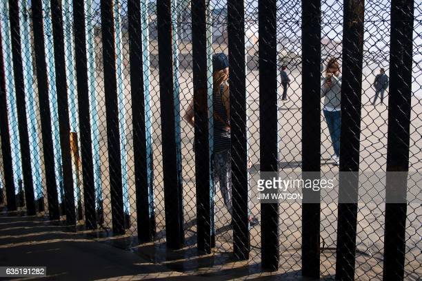 A girl takes a cell phone photo of another girl on the Tijuana Mexico side near the border fence separating the beaches at Border Field State Park in...