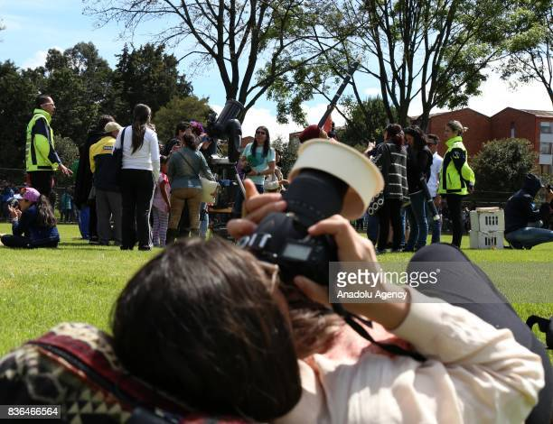 A girl takes a photo of the partial solar eclipse while others observe with a telescope at Ciudad Montes Park in Bogota Colombia on August 21 2017