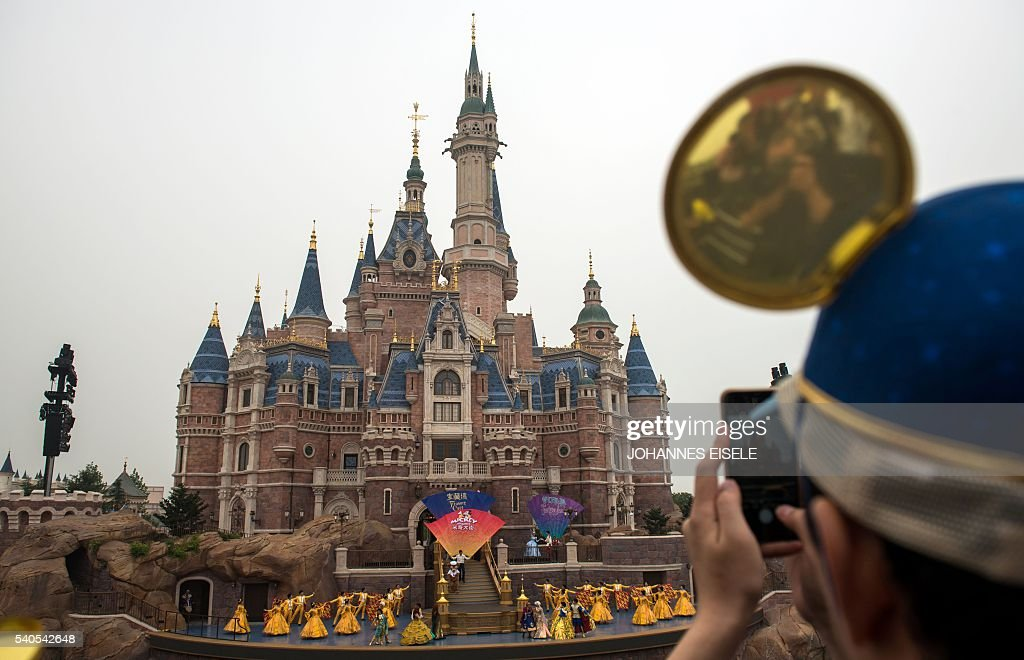A girl takes a picture of the Enchanted Storybook Castle during the opening ceremony of the Shanghai Disney Resort in Shanghai on June 16 2016...
