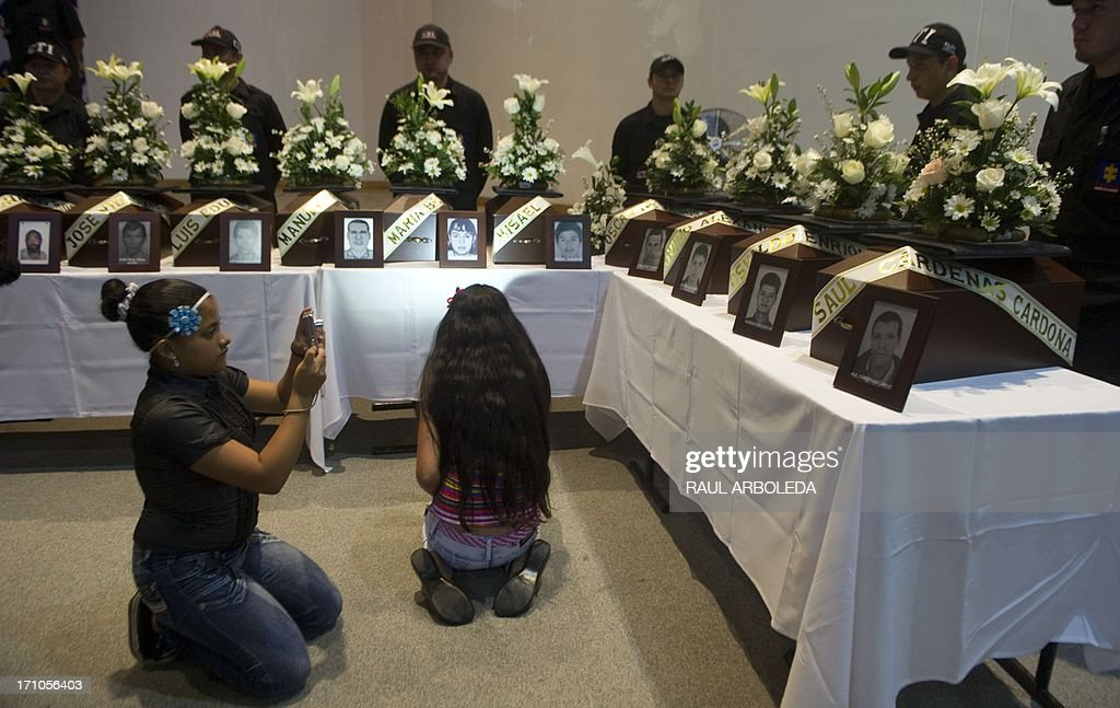 A girl takes a picture of the urn with the remains of his relative who was disappeared during the Colombian civil war until recently, on June 21, 2013 in Medellin, Antioquia department, Colombia. In a ceremony, relatives of 36 victims received the remains of their loved ones, which were recently found in common graves due to information given by demobilized combatants of both, leftist guerrillas and right-wing paramilitary groups, in the framework of the country's peace process. AFP PHOTO/Raul ARBOLEDA