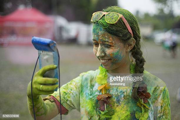 A girl takes a selfie at Color Run on April 30 2016 in Turin The Color Run is a noncompetitive event that takes place in Turin with music flowers and...