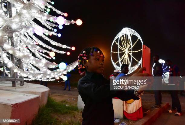 A girl takes a selfie photo in front of a Christmas tree decoration as residents enjoy an evening stroll on December 29 2016 in the business district...