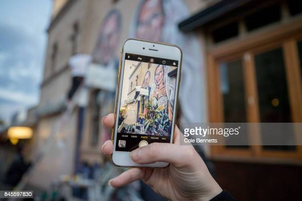 A girl takes an iPhone photo of a mural by artist Scott Marsh depicting former Prime Minister Tony Abbott in Redfern on September 11 2017 in Sydney...