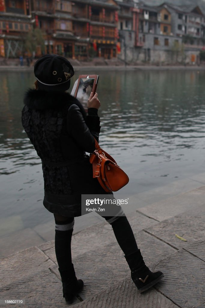 A girl takes photo by ipad by Tuojiang River on December 18, 2012 in Fenghuang, China. Fenghuang Town was built by Emperor Kangxi in 1704 and after 300 years, the city's ancient appearance has been well preserved. Hunan is located in southwest Hunan Provience of China with a population of 370,000 within a total area of 1700 square kilometers.