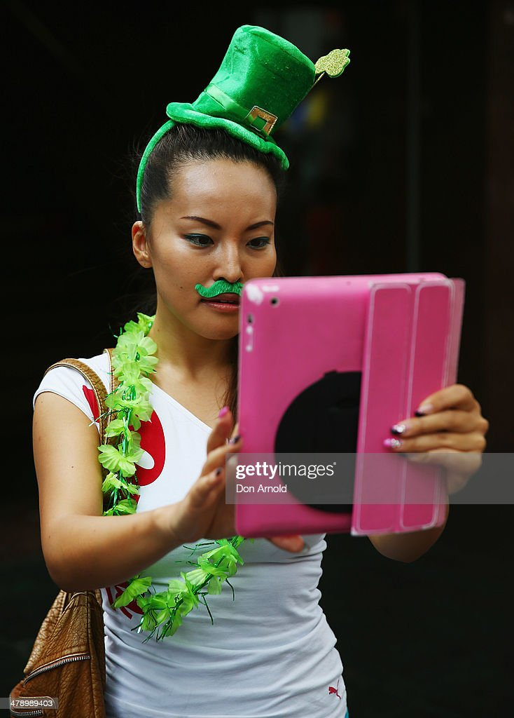 A girl takes photos of the parade on her Ipad on March 16, 2014 in Sydney, Australia. St Patrick's Day is an annual religious and cultural commemoration of the widely recognised patron saint of Ireland, Saint Patrick. March 17th, is a public holiday in Northern Ireland and the Republic of Ireland but is celebrated in many countries around the world where Irish diaspora have settled.