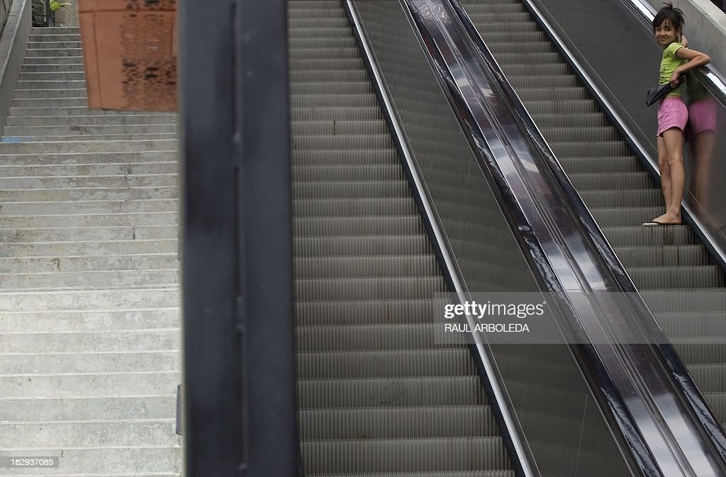 """A girl takes the escalators at Comuna 13 neighbourhood, one of the poorest and most violent areas of the northeastern Colombian city of Medellin, Antioquia department, Colombia on March 1, 2013. Medellin, which competed with New York and Tel Aviv, was chosen by popular vote through the internet, as the """"Innovative City of the Year"""" during the City of the Year contest, organized by The Wall Street Journal and Citigroup. The distinction was basically made for its modern transportation system, its public library, escalators built in a shantytown and schools that have allowed the integration of society. AFP PHOTO/Raul ARBOLEDA"""