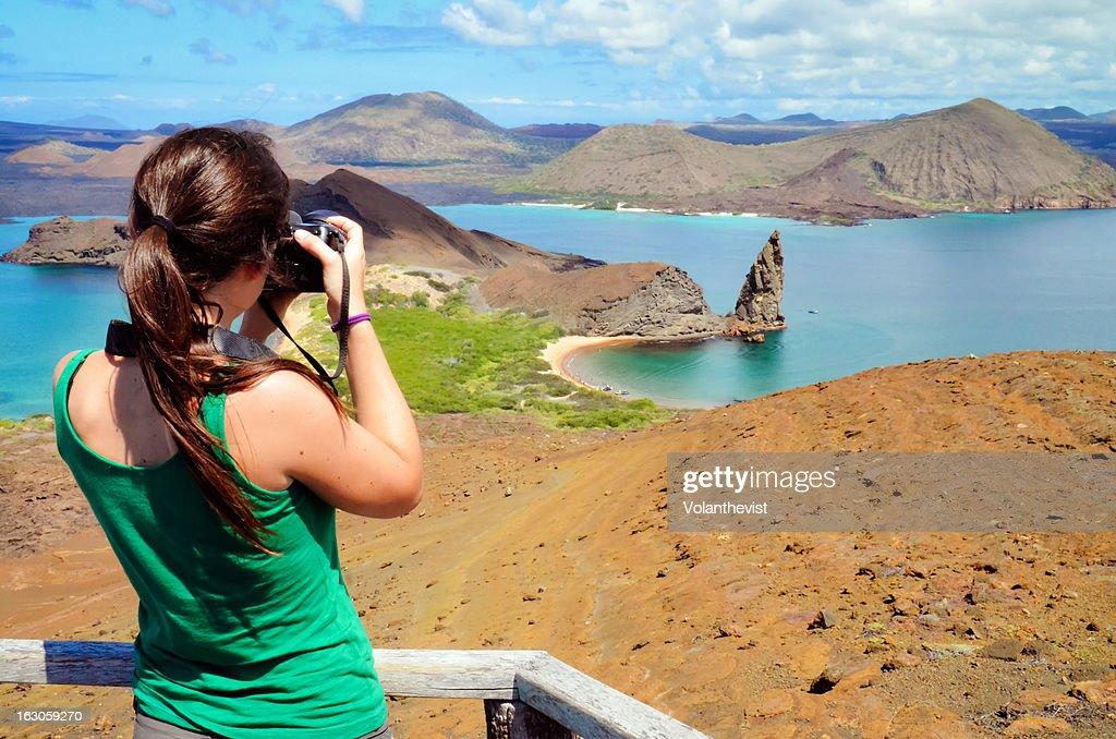 Girl taking a picture of Pinnacle Rock, Galapagos