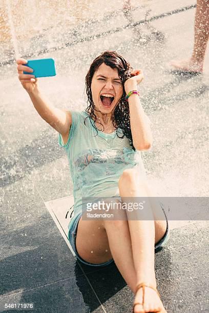 Girl taking a selfie under a fountain