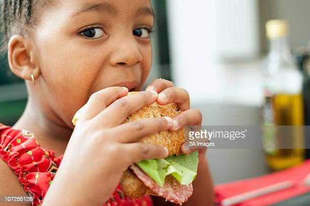 Girl (4-5) taking big bite of sandwich