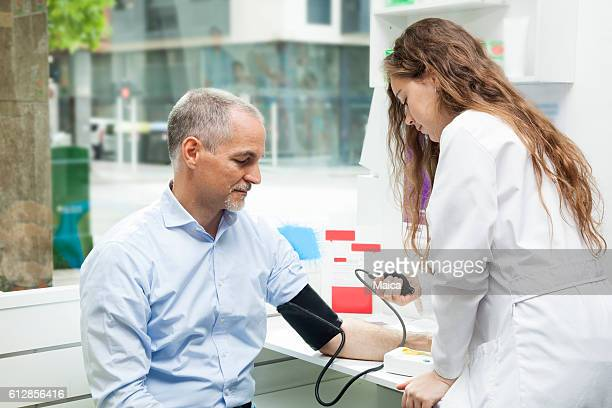 Girl taking blood pressure to mature man