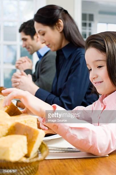 Mädchen mit Brot, während Eltern sagen grace