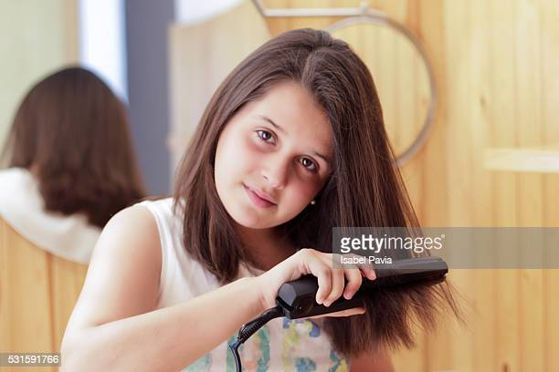 Girl taking care of her hair in domestic bathroom