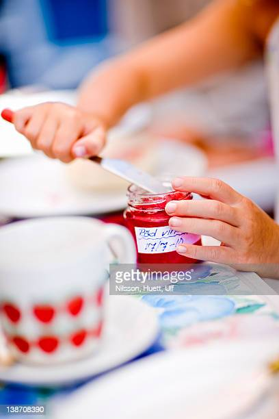 Girl taking jam from bottle with knife, close-up