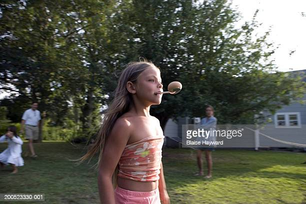 Girl (6-7) taking part in egg and spoon race