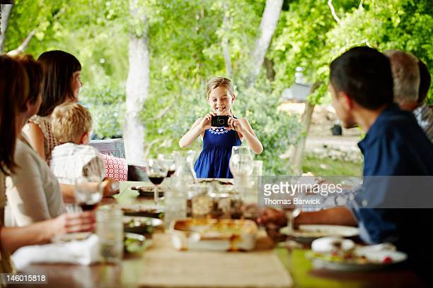 Girl taking photo of family seated for meal