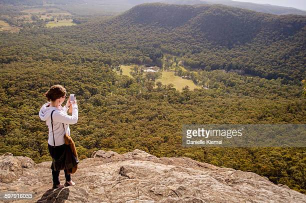 Girl taking photo with mobile of a mountain view
