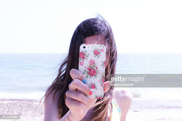 Girl (12-13) taking photo with smartphone