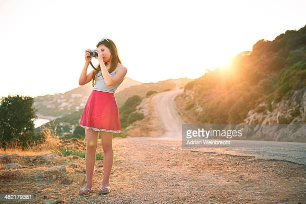 Girl taking photographs at sunset, Kas, Turkey