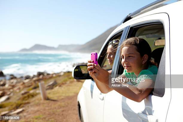Girl taking picture from car window