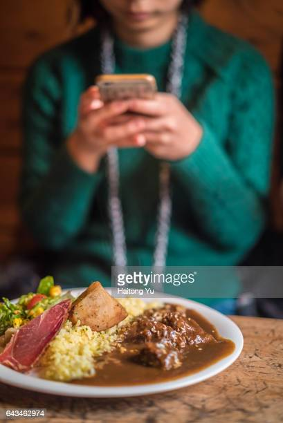 Girl taking pictures of a Japanese-style venison curry