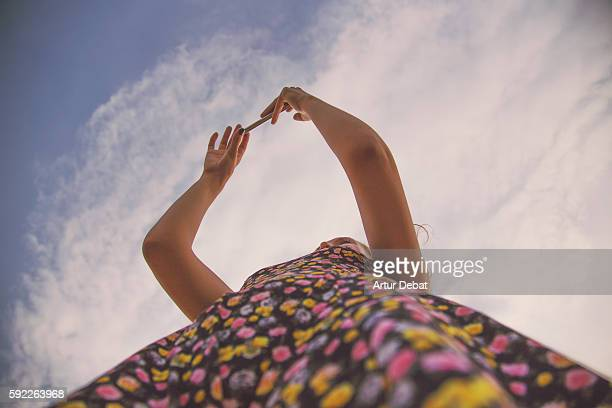 Girl taking pictures with smartphone visiting the Cap de Creus region in Costa Brava taken from below view with the sky and colorful dress.