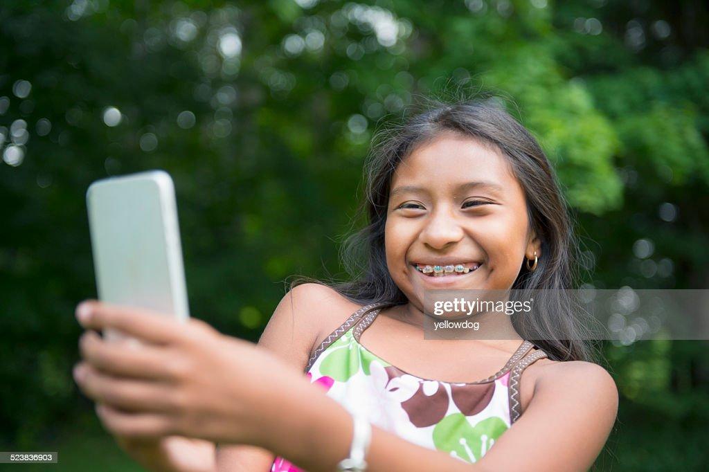 Girl taking selfie in garden