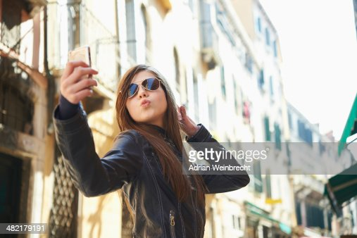 Girl taking selfie on smartphone, Venice, Italy