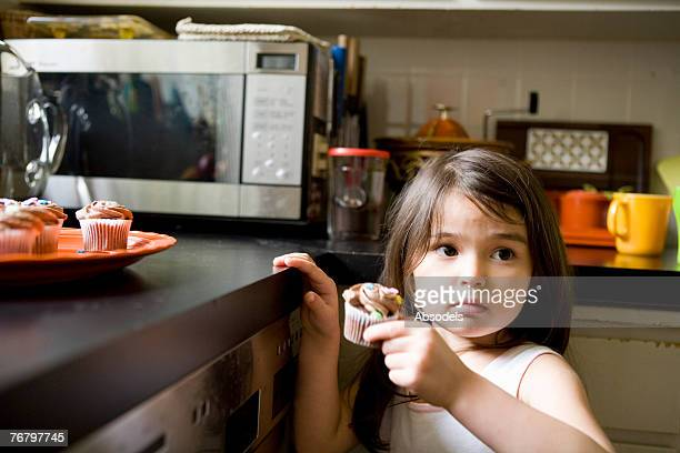 A girl taking some foods in a kitchen