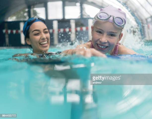 Girl taking swimming lessons with a teacher