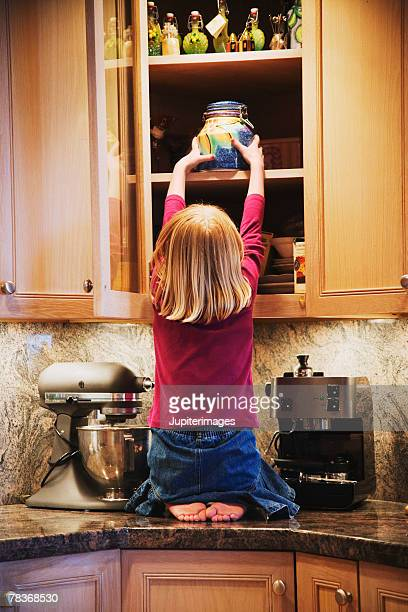 Girl taking treats out of cabinet