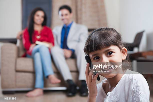 Girl talking on a mobile phone with her parents sitting in the background