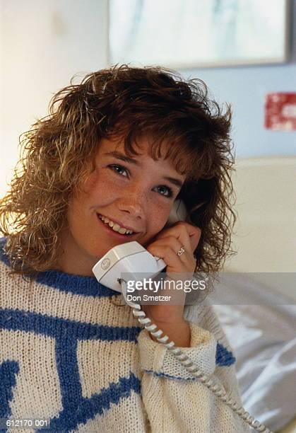 Girl (11-13) talking on telephone, blue and white jumper