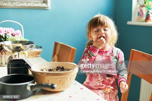 Girl tasting baking ingredients in kitchen
