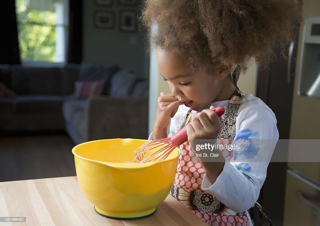 Girl tasting cupcake batter : Stock Photo