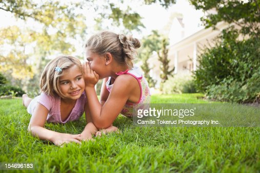 Girl telling younger sister a secret : Bildbanksbilder