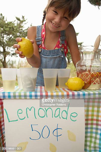 Girl (5-7) tending lemonade stall, holding lemon, smiling, portrait